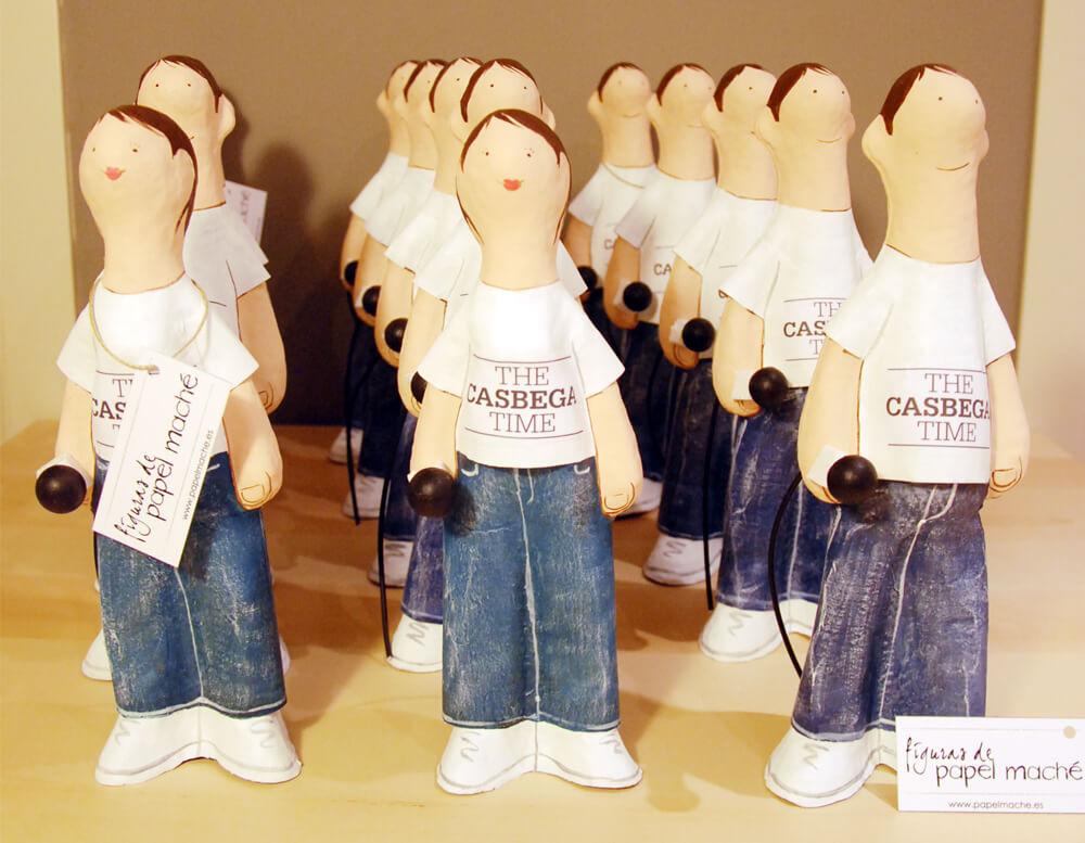 Grupo de figuras de papel maché representando a periodistas con un micro